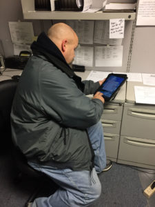 Reviewing the tablet to see what jobs are on the schedule.