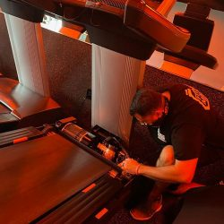 Technicians servicing treadmill in Orangetheory